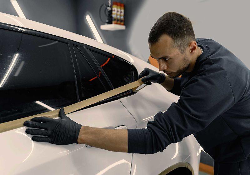profissional aplicando uma fita antes de efetuar a pintura